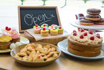 Close-up of various sweet foods on table with open signboard in cafeteria